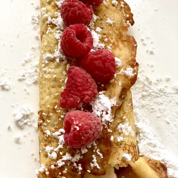Golden brown crépes filled with fruit and nutella and topped with raspberries and powdered sugar