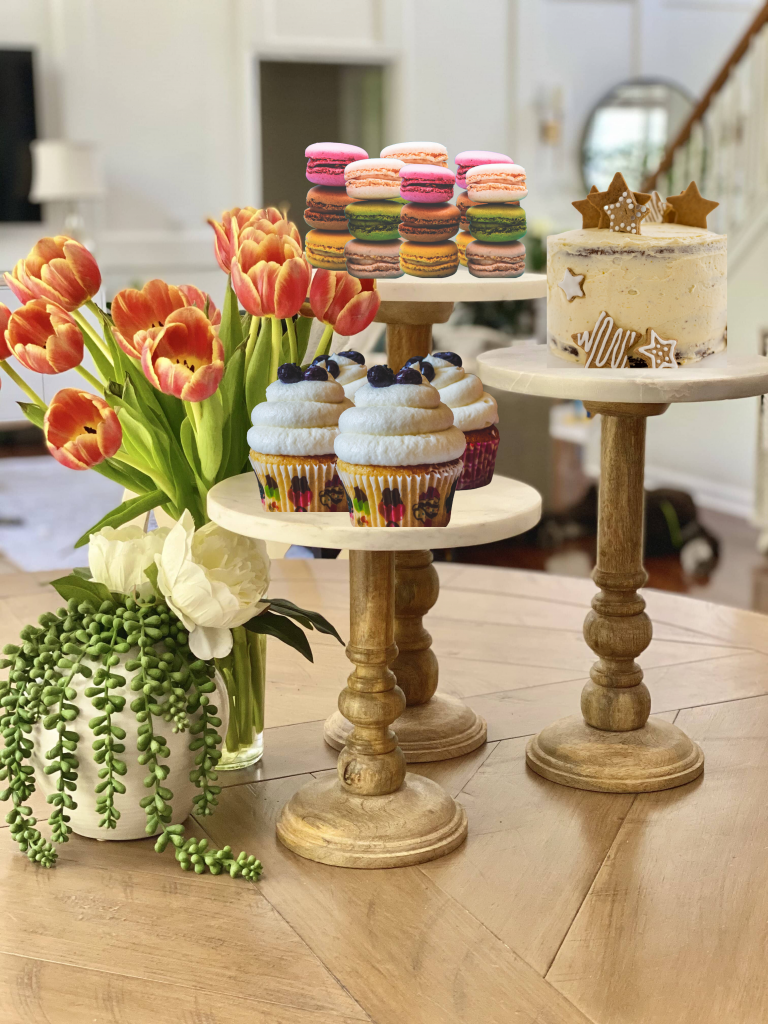 Wooden pedestal with marble top as a center piece holding desserts