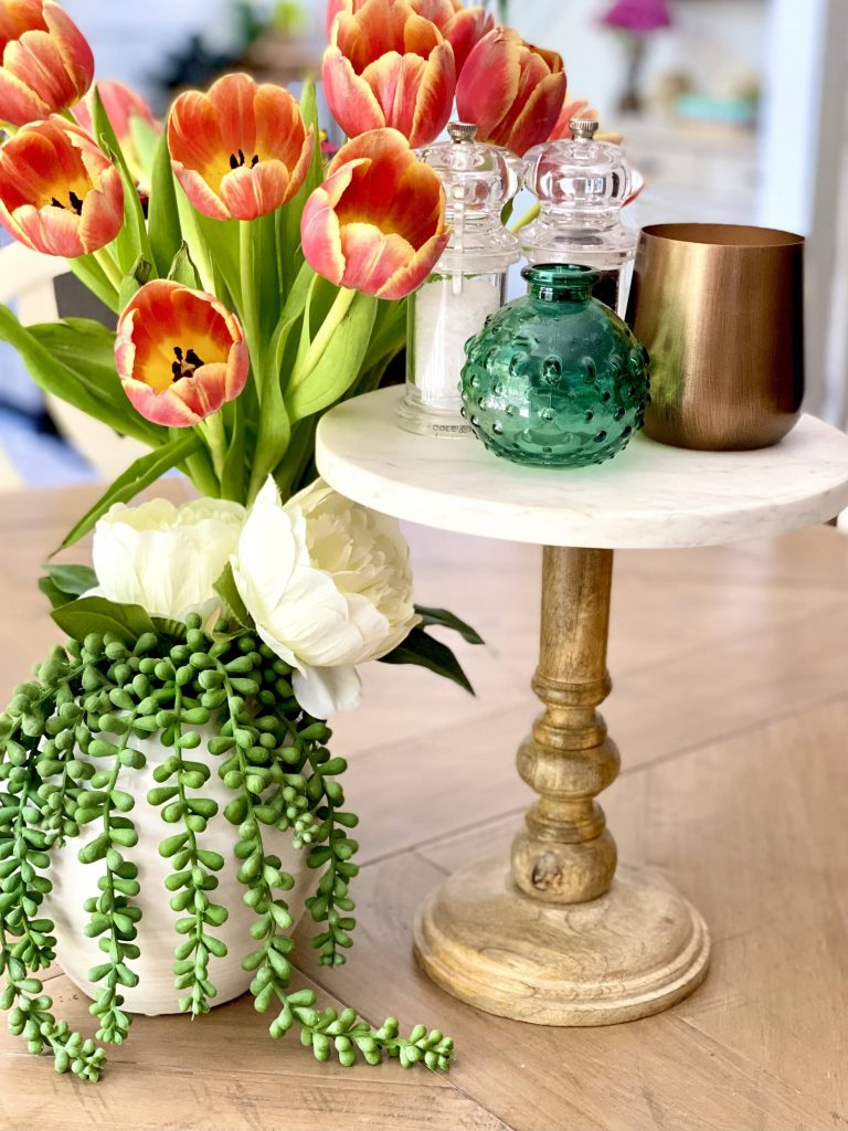 Wooden pedestal with marble top as a cernterpiece holding salt, pepper, and a candle