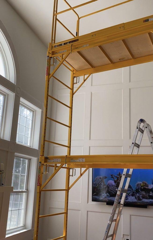 scaffolding in our living room for installing a two-story recessed panel wainscoting